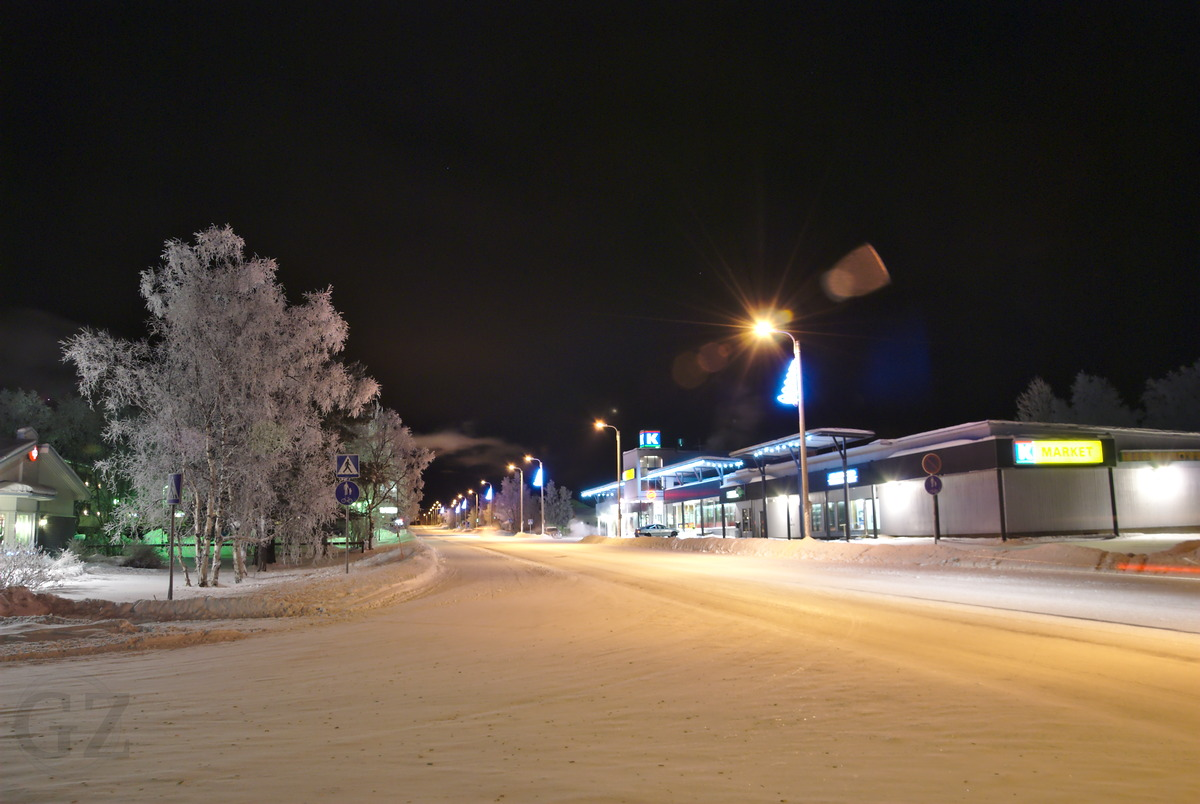 village center with grocery shop and snow covered road