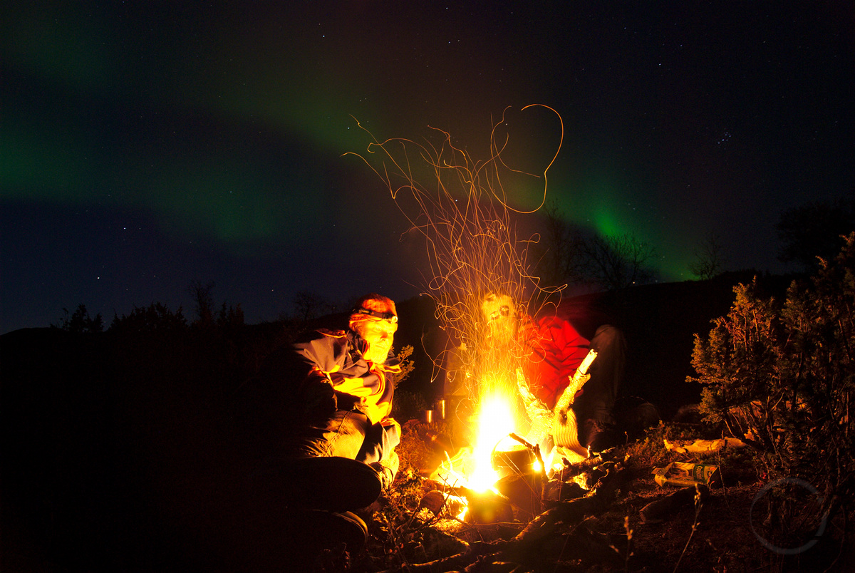 Two people sitting next two camp fire, with nothern lights in the background