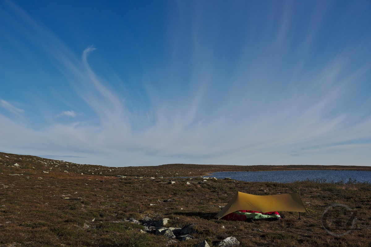 Tarp and camp site in front of tundra lake