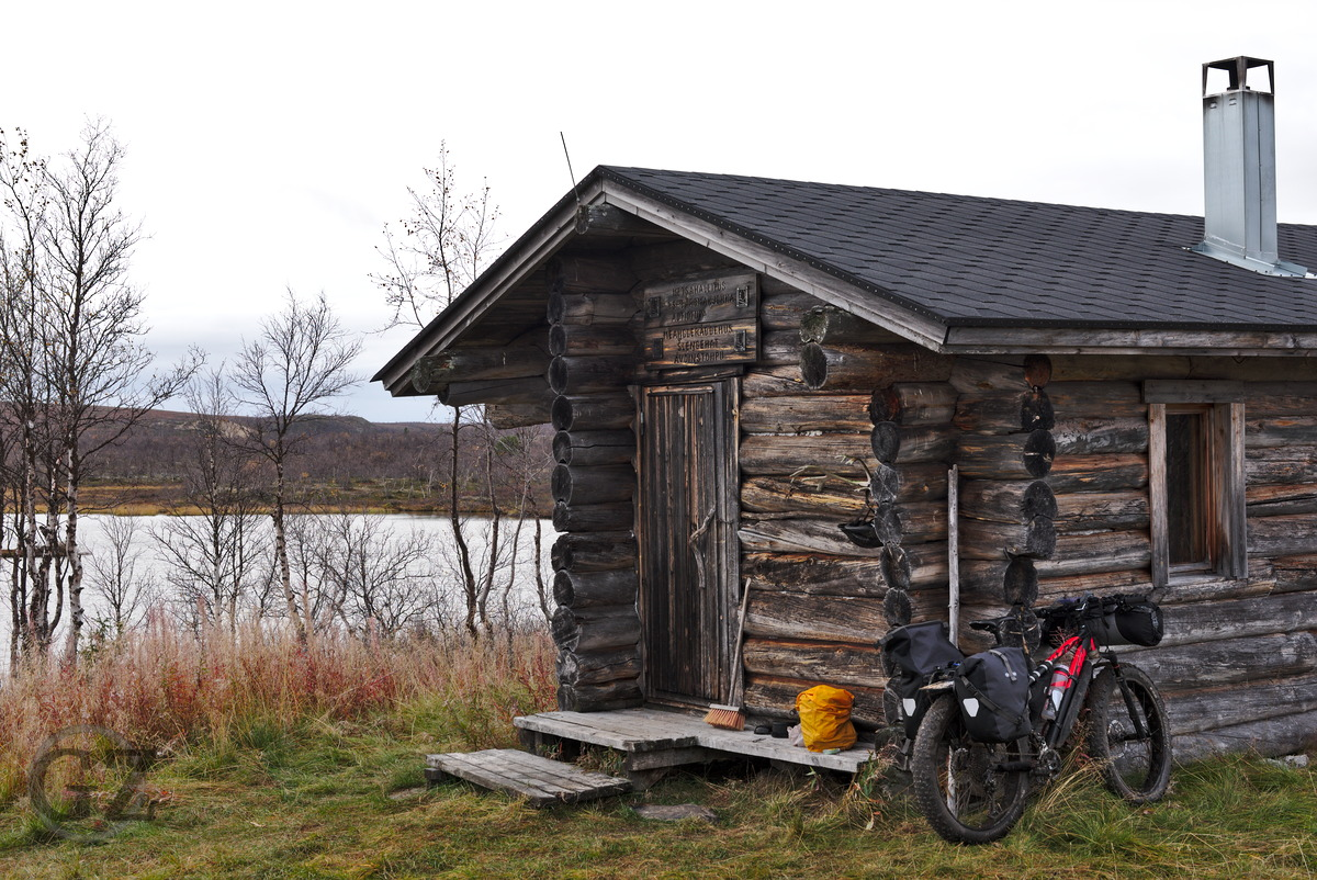 Bike leaning to wooden cottage near lake shore
