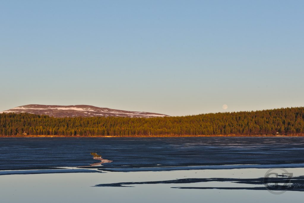Moonrise over haf-frozen lake Ounasjärvi
