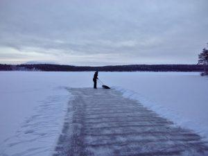 Person shoveling snow on lake