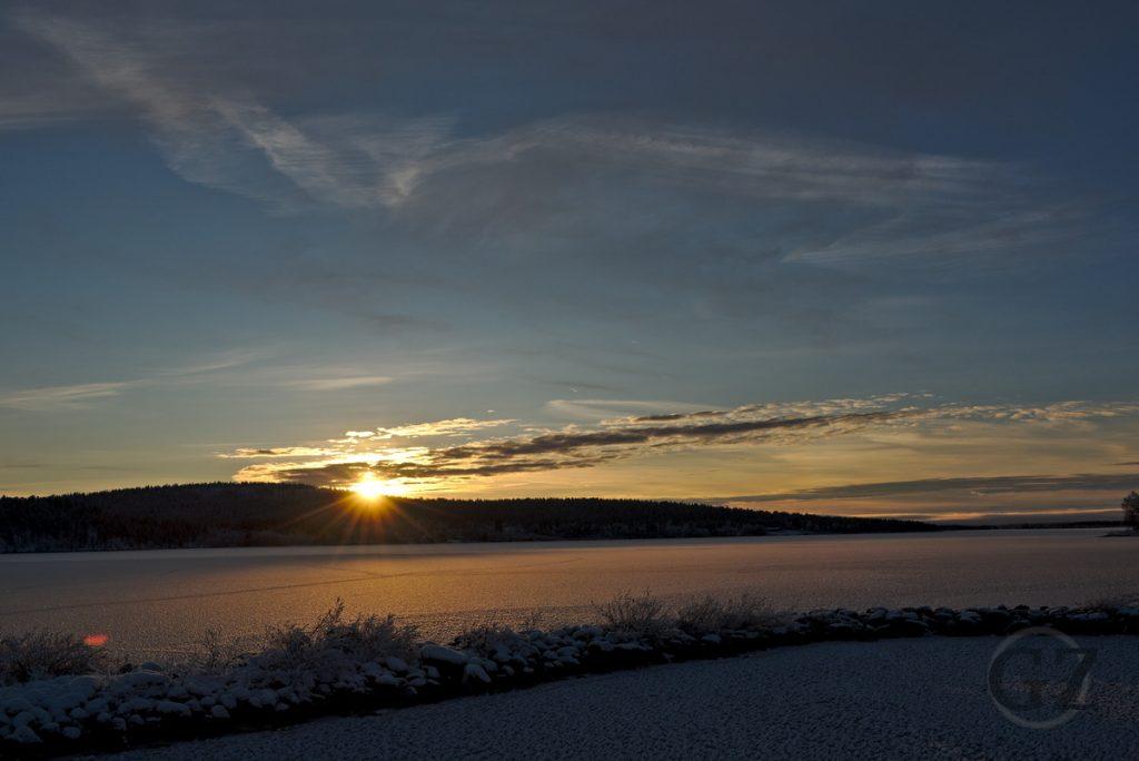 sun setting behind frozen lake